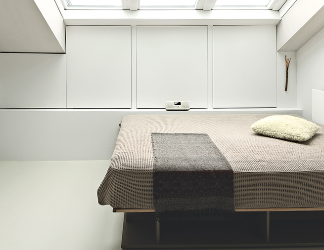 Minimalist bed beneath a skylight.