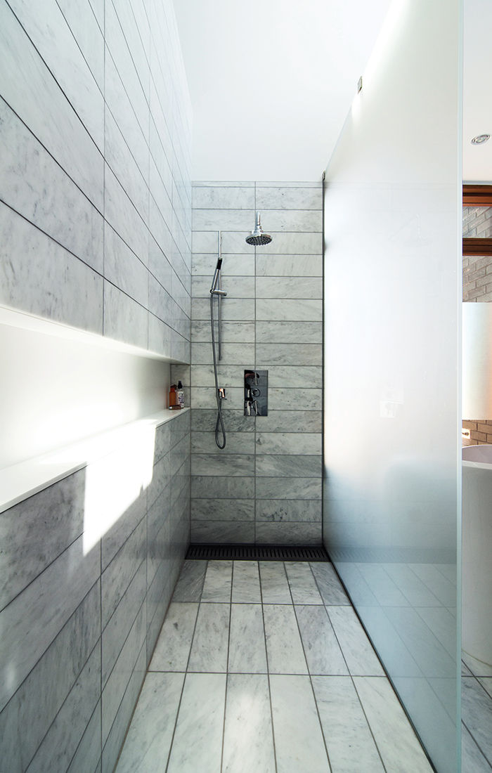 Standing shower with glass panels and stainless steel hardware