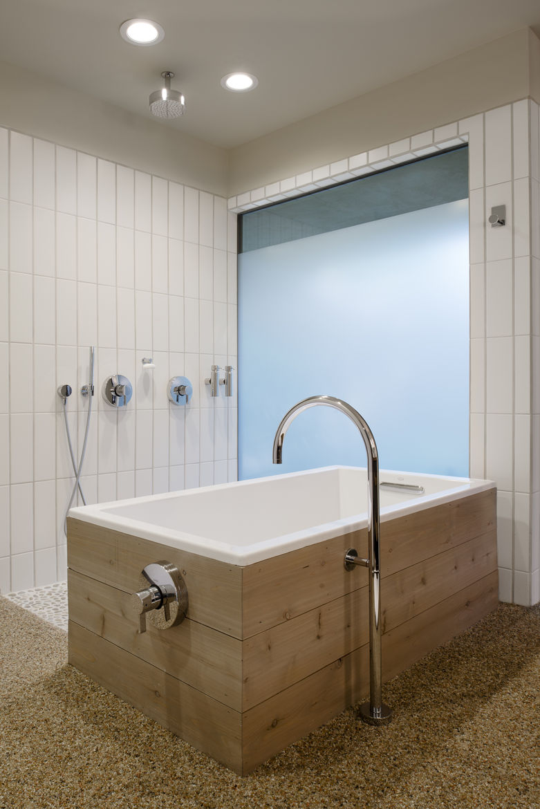 Master bath with freestanding tub lined in wood