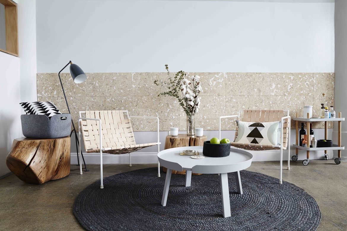 Dots office sitting area with woven chairs, wood stools, and bar cart