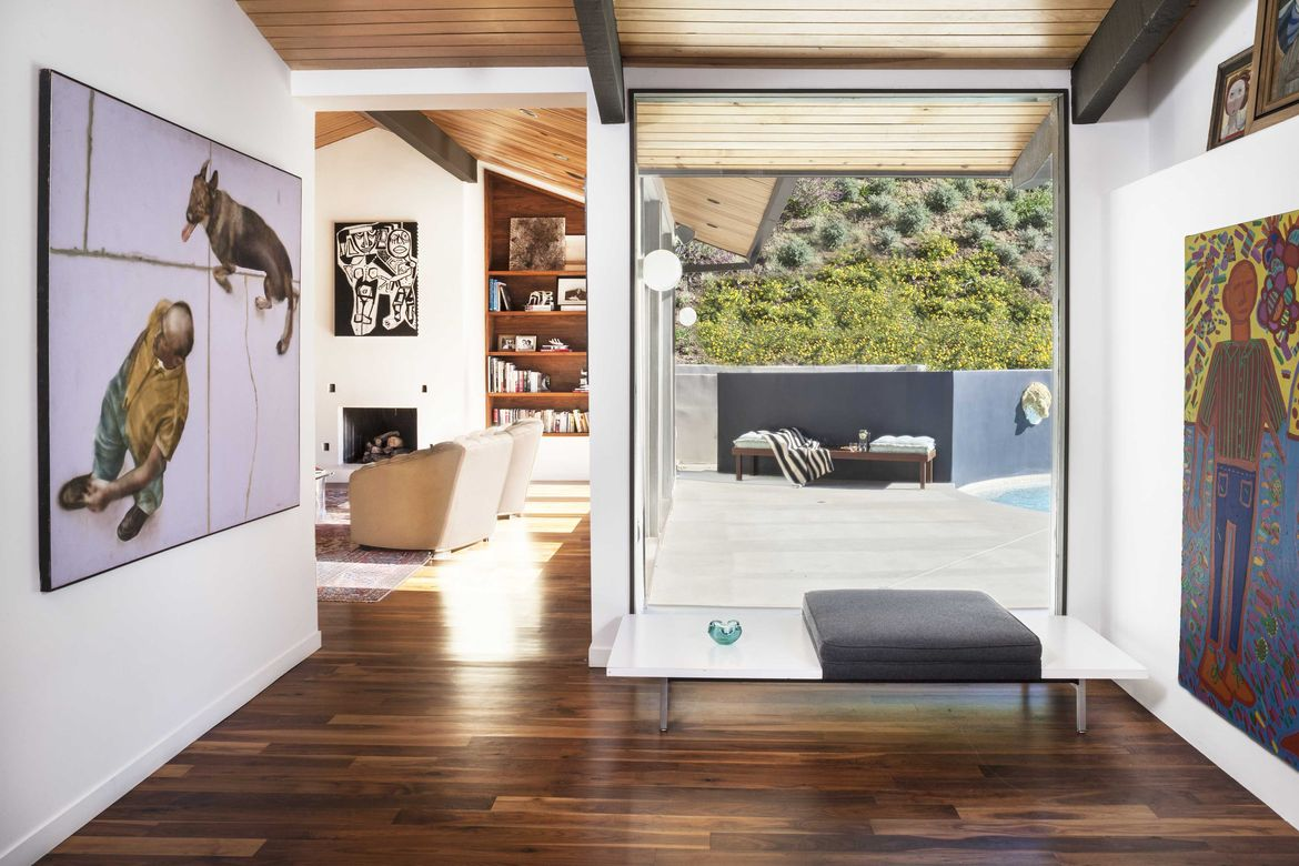 Midcentury renovation in Brentwood with paintings and Herman Miller bench