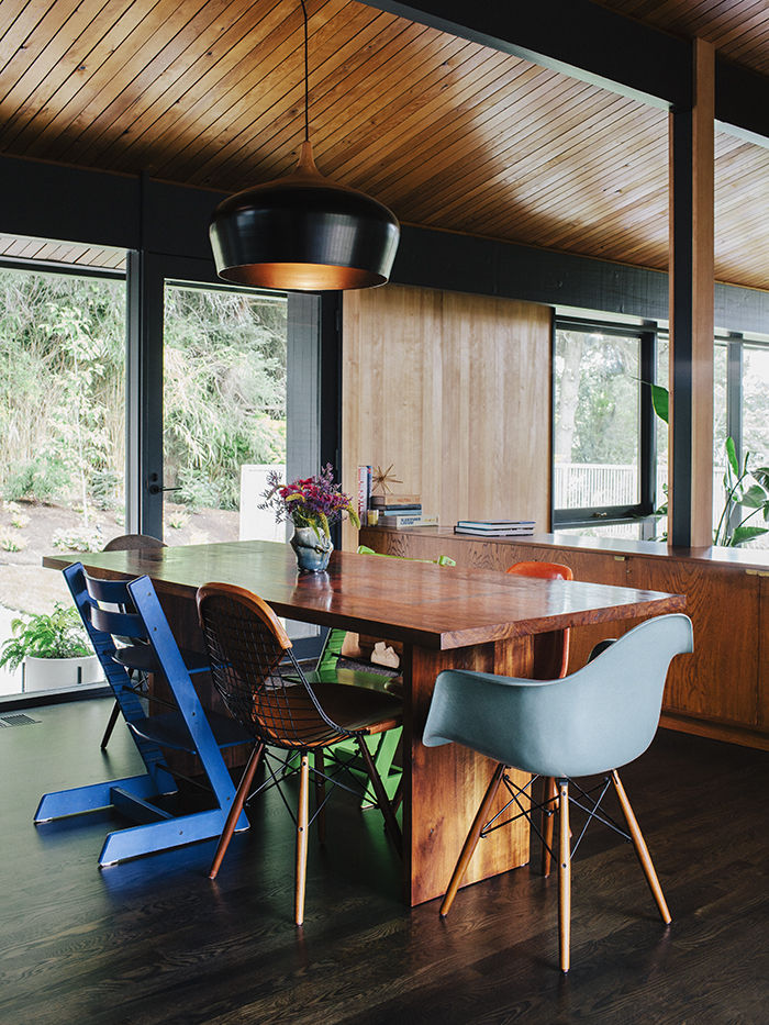 Mix and match dining chairs around wood table with pendant lamp in Dwell magazine