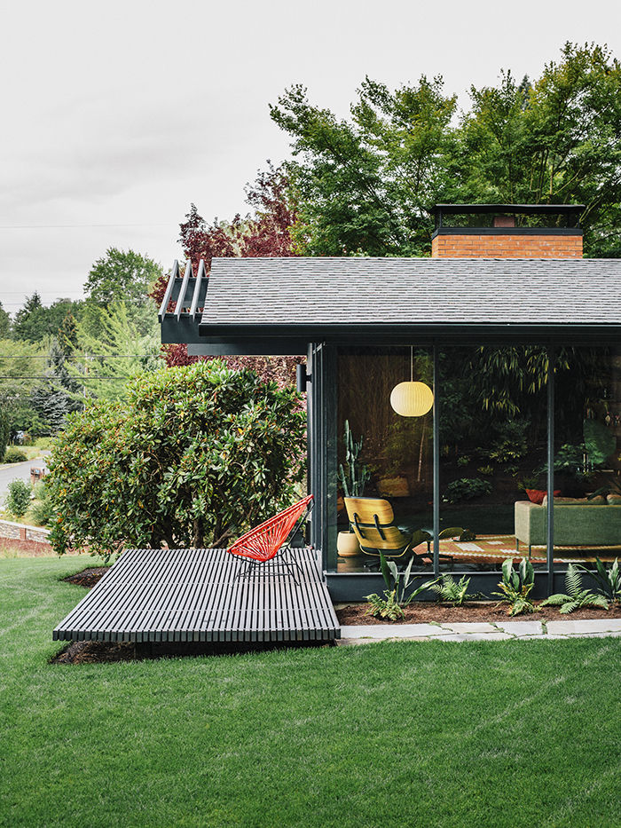 Glass walls and wood patio on midcentury Portland house painted black