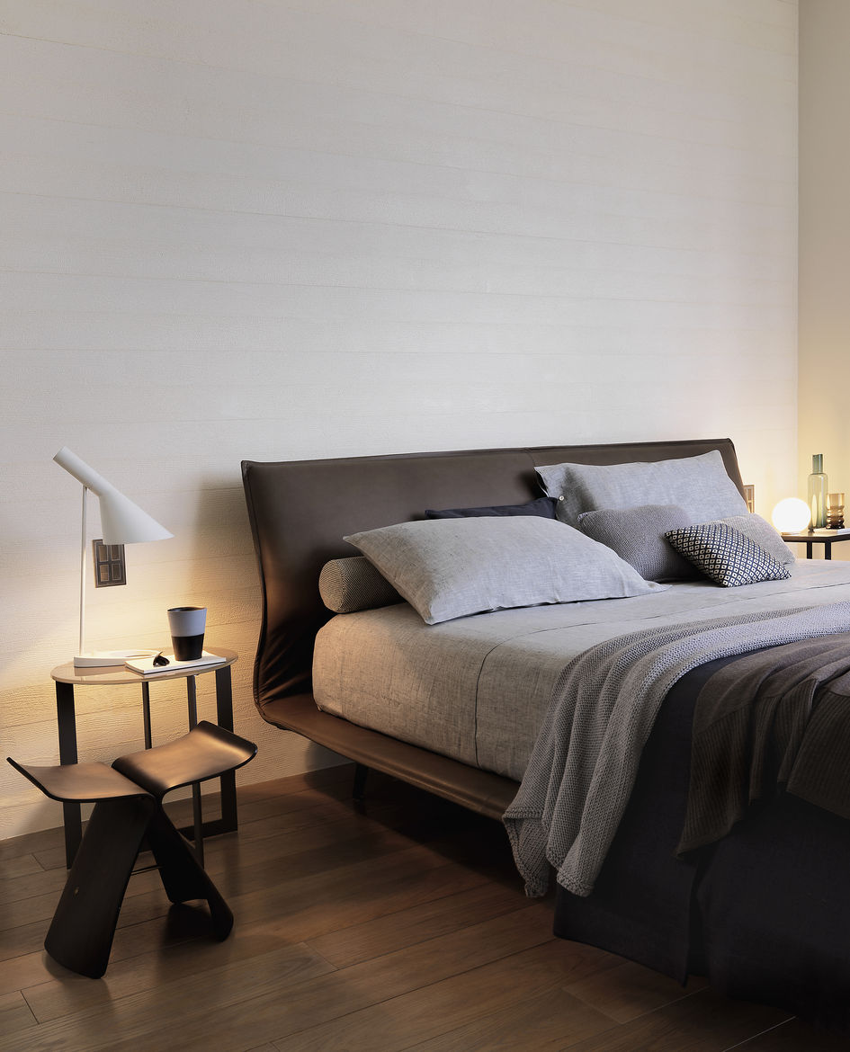 Homey bedroom lit with warm lights and decorated in neutral colors.