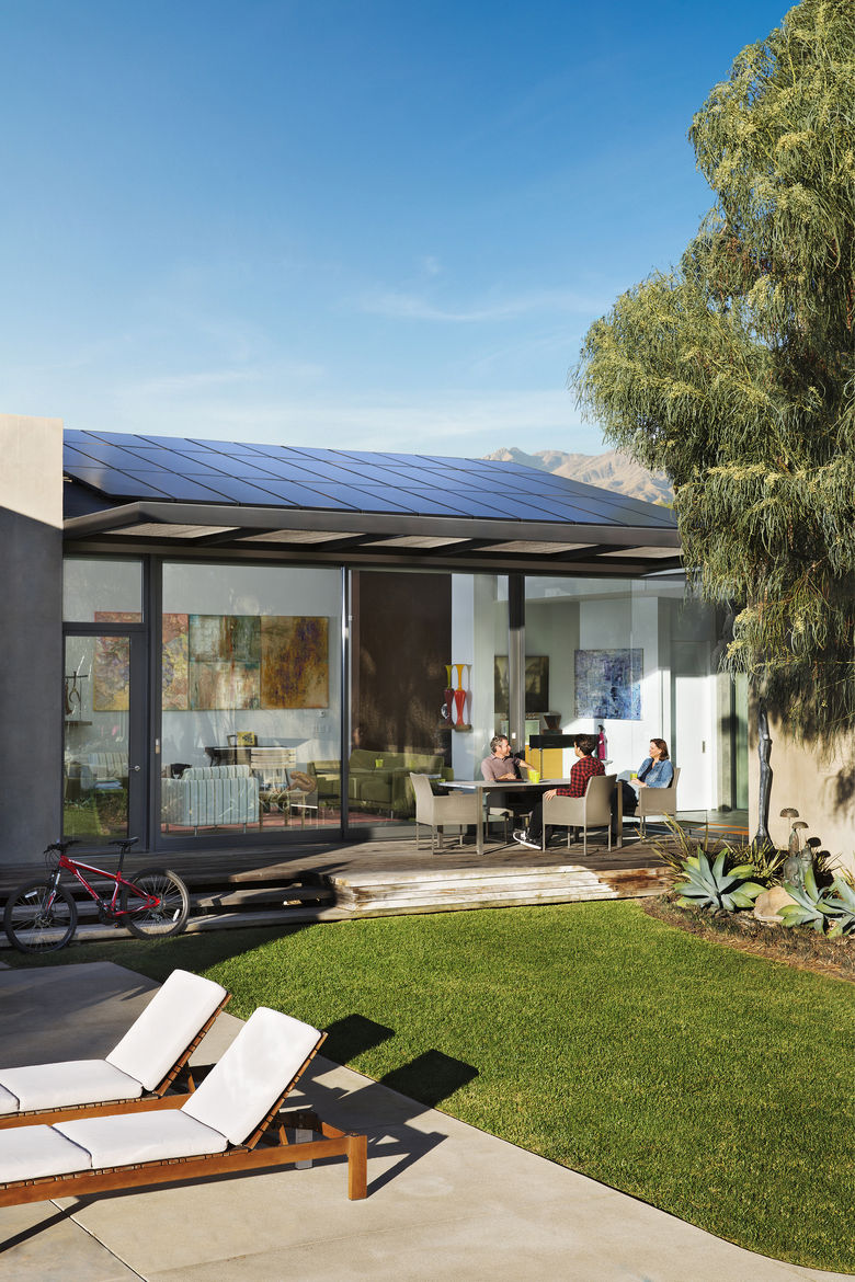 Backyard view of home with solar panels
