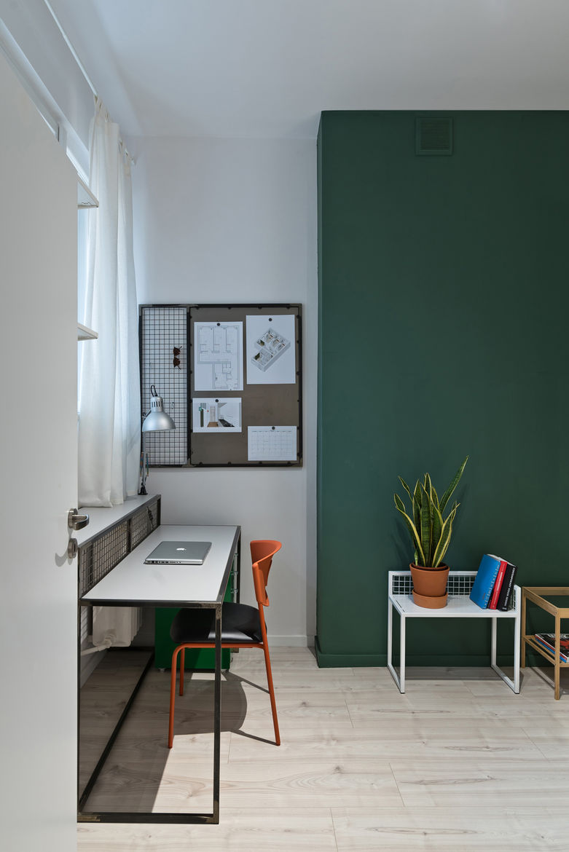 Orange IKEA chair, green accent wall, and custom furniture in Polish apartment.