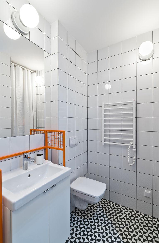 Graphic Vives floor tiles and custom-made orange sink frame.