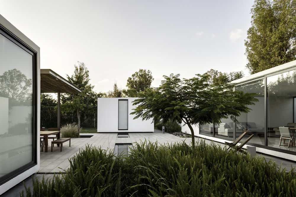 Courtyard with cooling shade and water feature of weekend home by Asociacion de Diseno in Mexico.