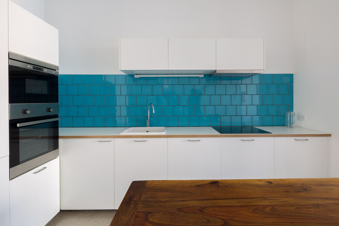White kitchen cabinets with a blue tiled backsplash
