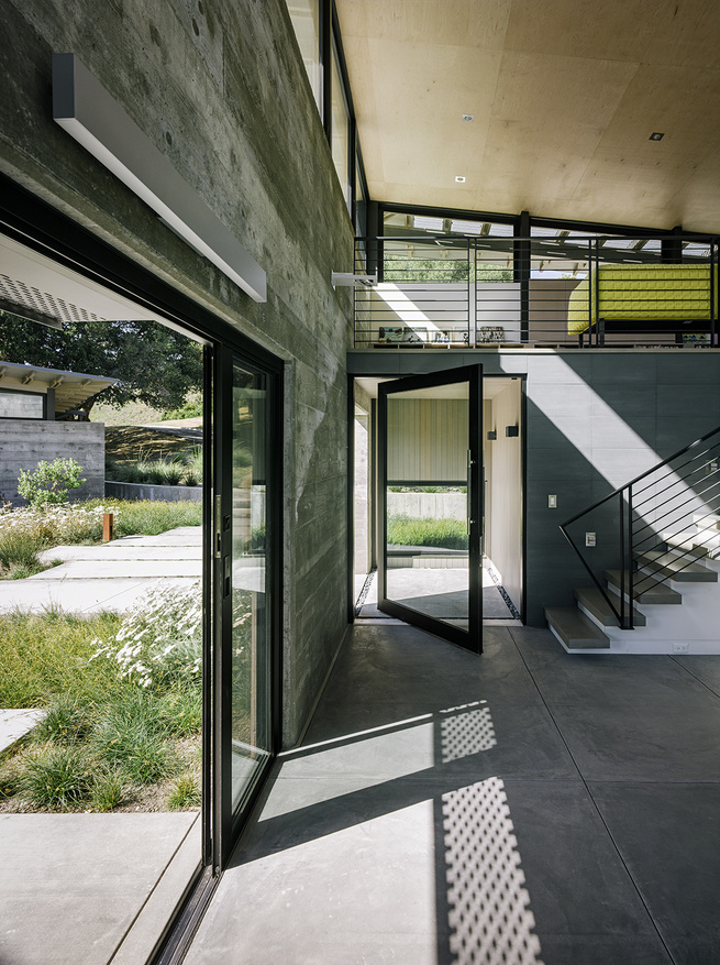 Entryway of modern eco-conscious pavilion in California by Feldman Architecture with Fleetwood glass windows, furnished with Ligne Roset sofa.