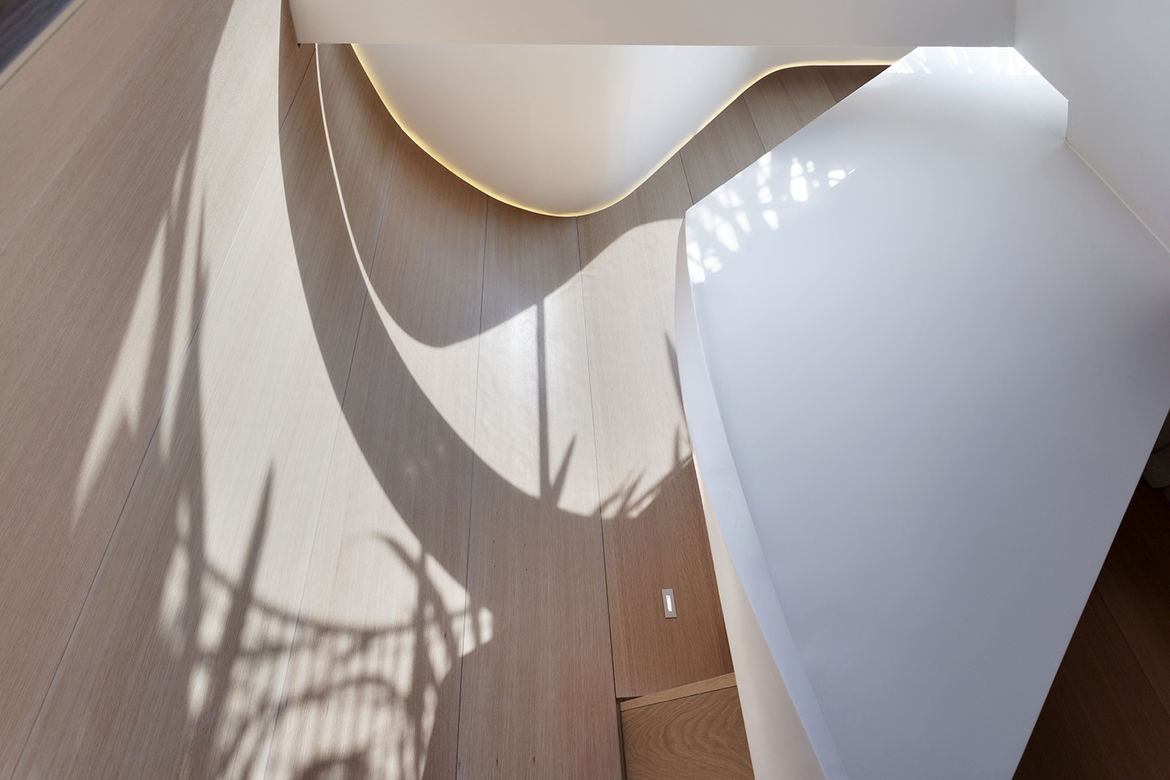 Dramatic white staircase in a narrow house
