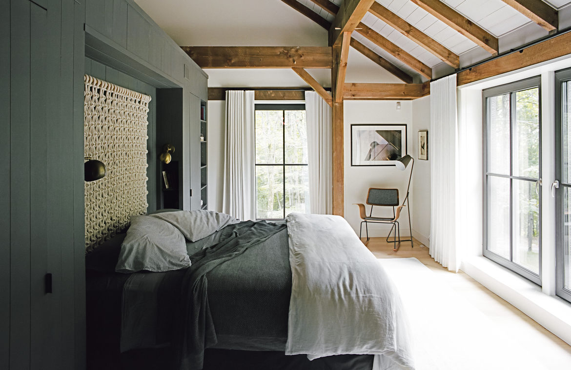 The master bedroom features brass details and a textured wall hanging.