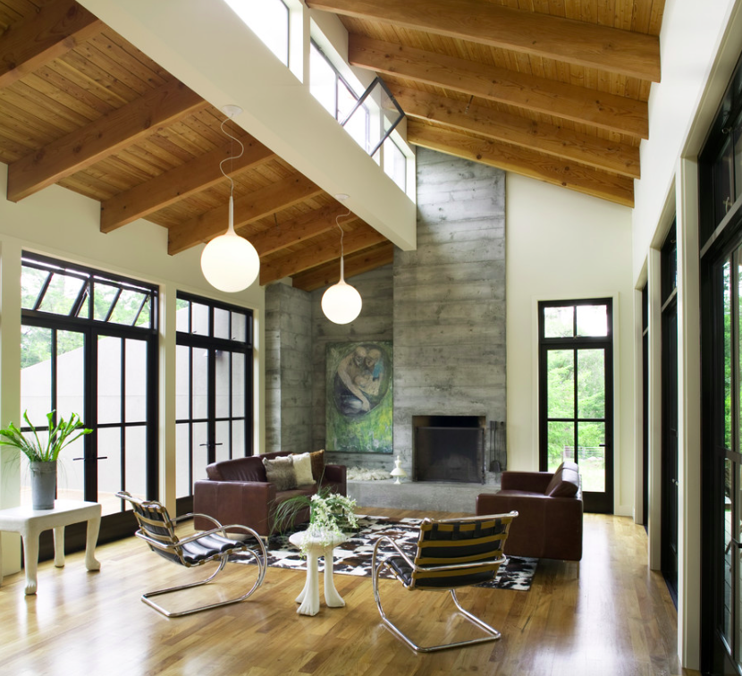 Living room with teak flooring and a concrete fireplace