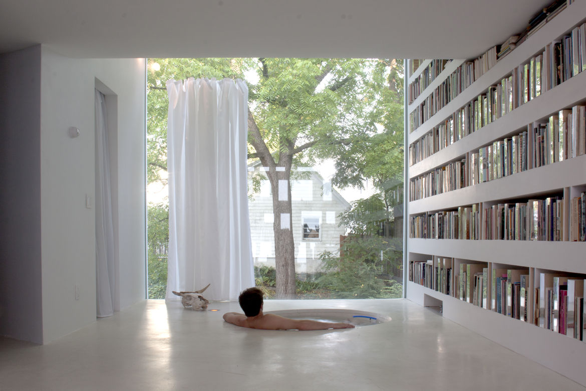 Haffenden house library with bookcase and bathtub.