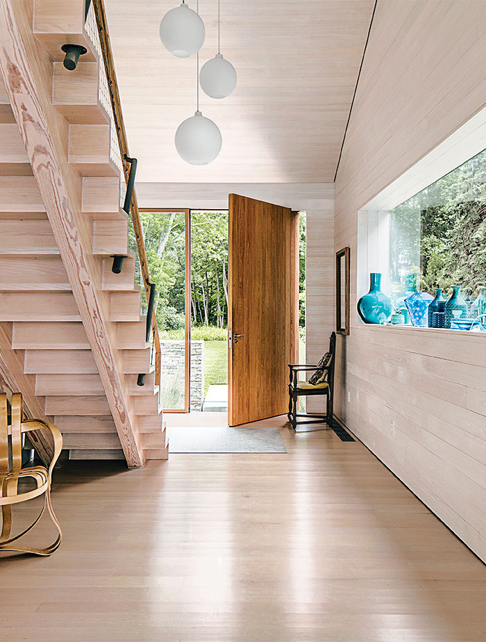 Modern Connecticut summer home renovation with oversize door with pivot hinge in the entry