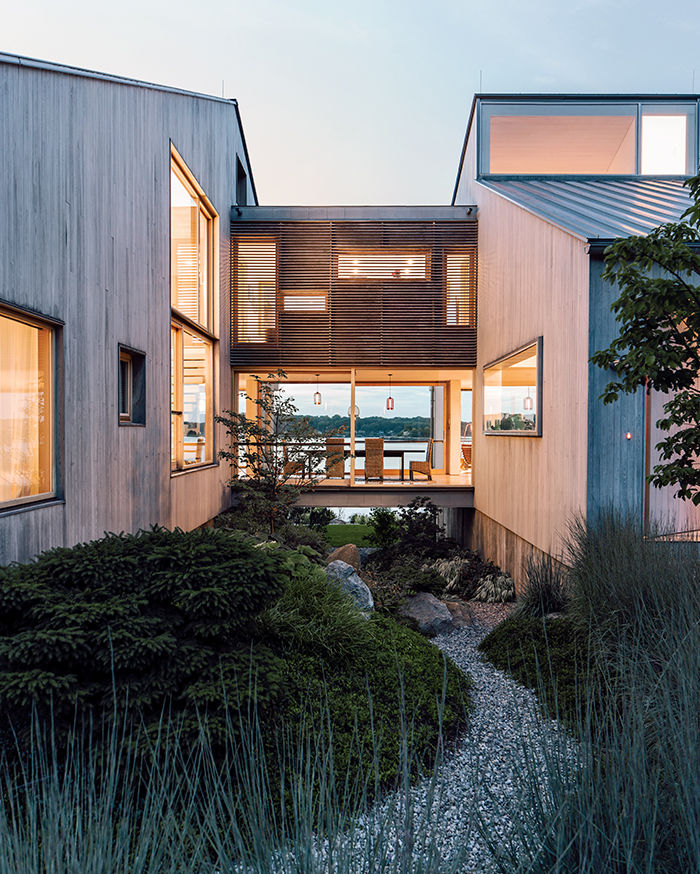 Modern Connecticut summer home renovation with bleached cedar siding on the volumes connected by glass bridge