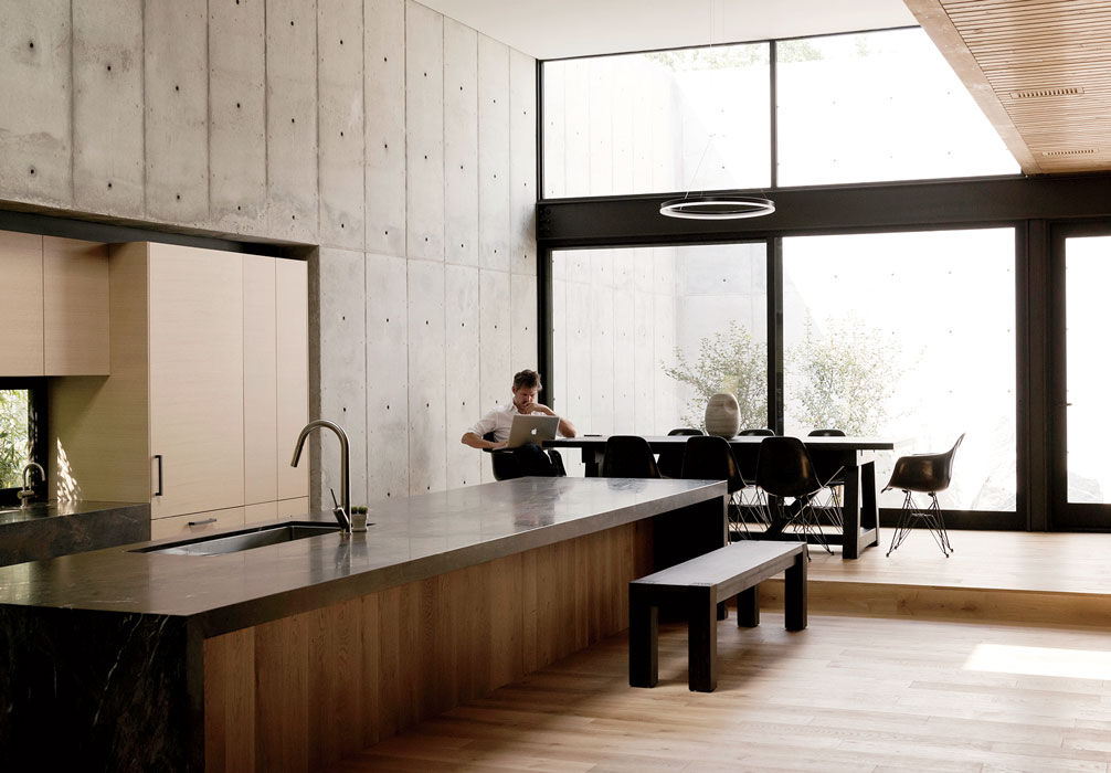 Modern Texas home kitchen with concrete walls, european white oak, Capolavoro granite countertop with Anotolini leather accent, and Verenna oak cabinets