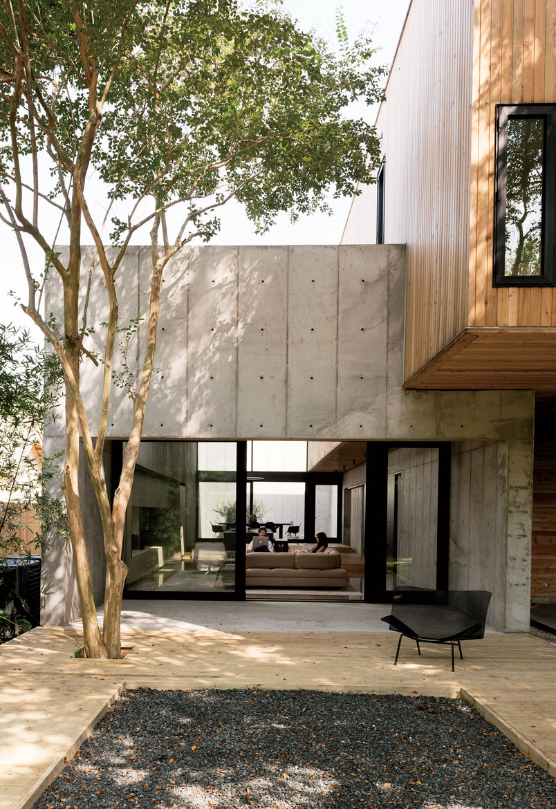 Modern Texas home outdoor deck and living room with Western Window Systems sliding doors, pine planks, and black gravel pit