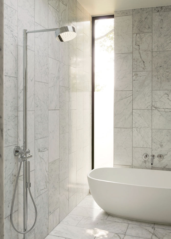Modern Texas home master bathroom with Bianco Venation marble, ADM tub, and Hansgrohe showerhead