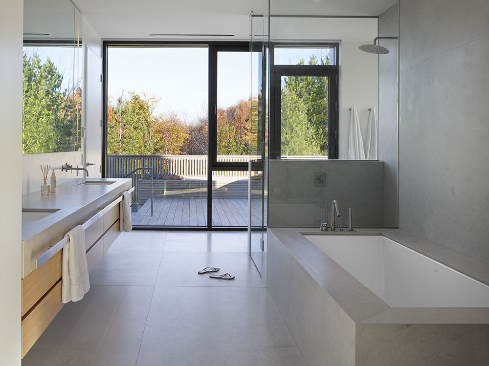 Boffi Minimal Series fixtures in bathroom that opens to deck and outdoor hot tub.