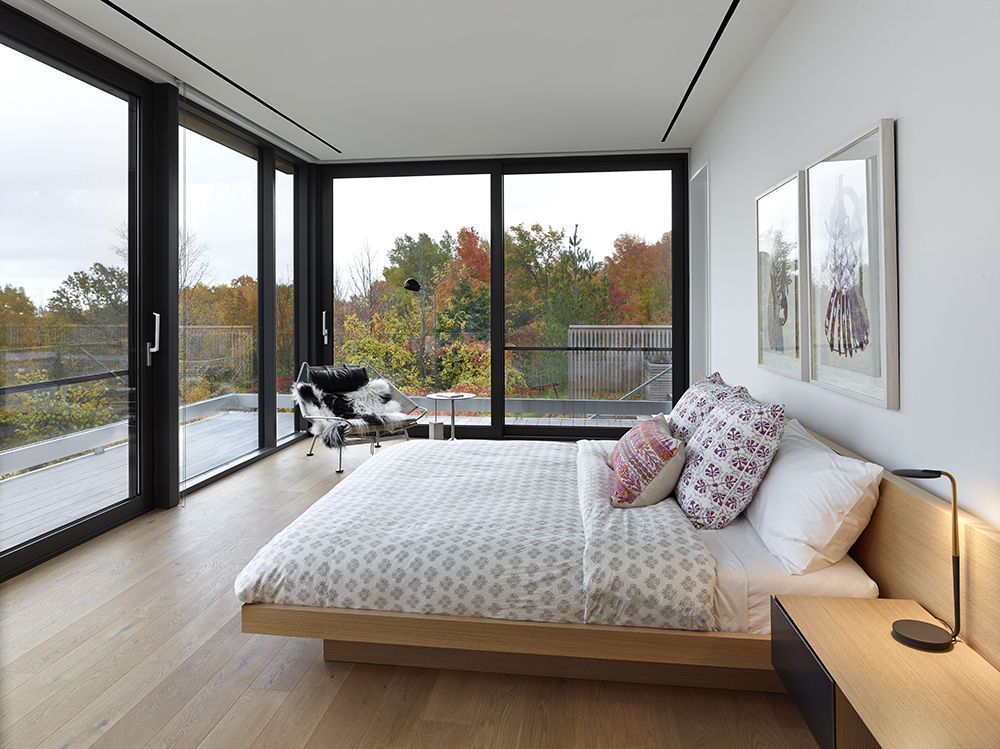 PP Møbler Flag Halyard Chair by Hans Wegner in bedroom with forest views.