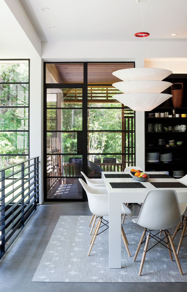 Upstate New York small sustainable retreat for Chilewich and Sultan dining area with cappallini table, eames chairs, ingo mauer pendant, and chilewich floor coverings