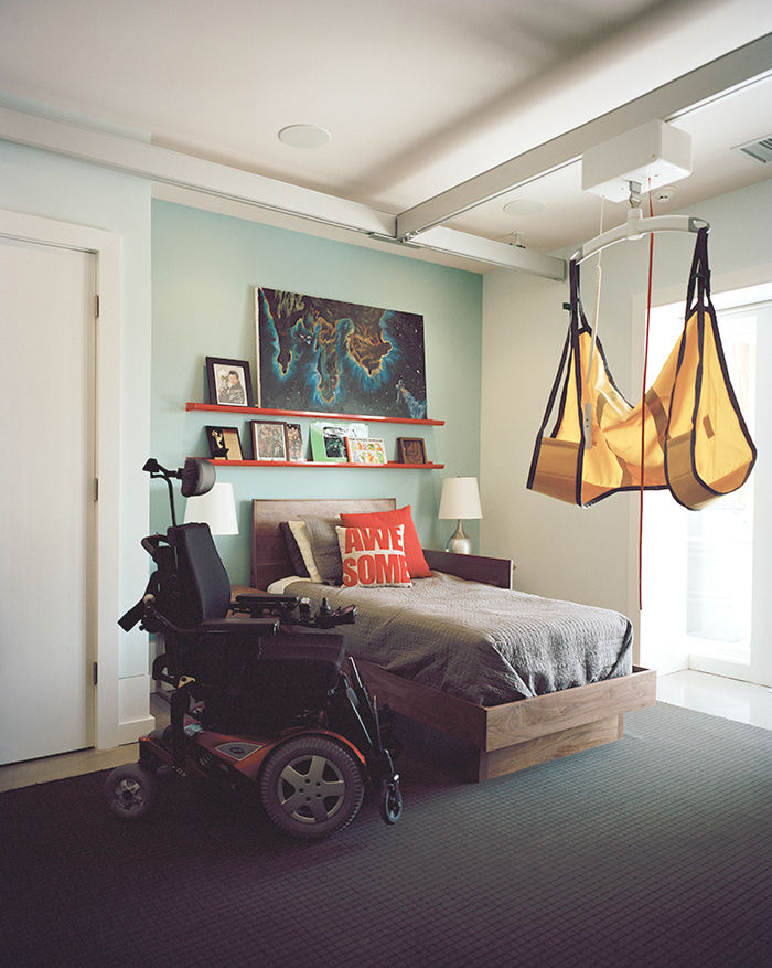 Modern universal design home in Baltimore with Guldmann lift system, room & board bed and atlas industries bookshelves in the bedroom