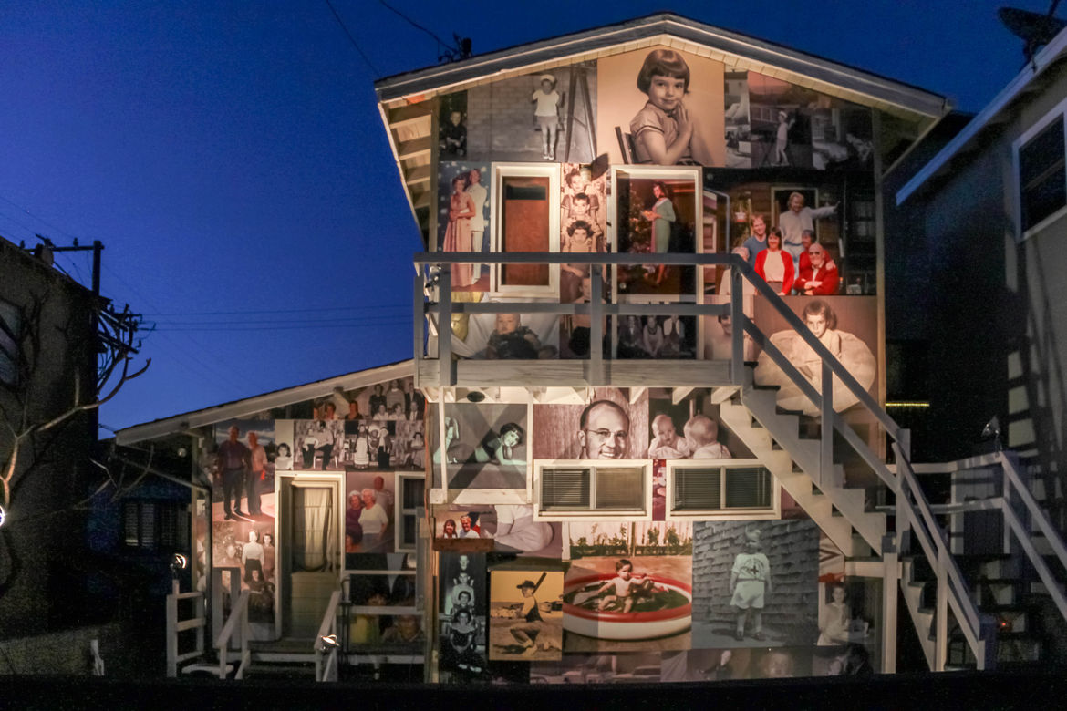 Manhattan Beach house at night covered in family photos