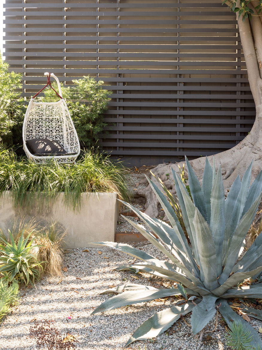 An Egg swing from Patricia Urquiola's Maia collection for Kettal sits in this garden.