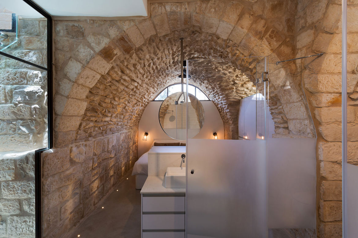 Master suite below a stone archway in a renovated home in Israel