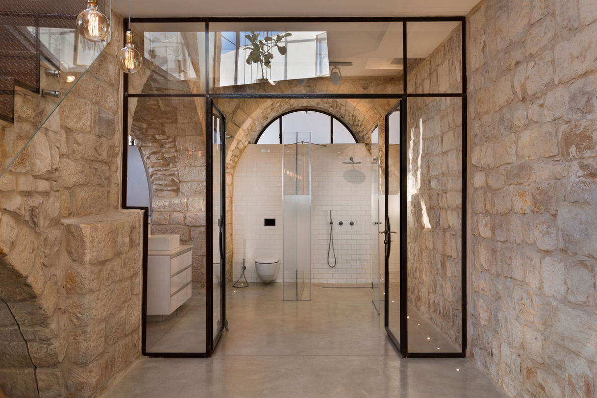 Glass and steel doorway leading to master bathroom in a renovated home in northern Israel