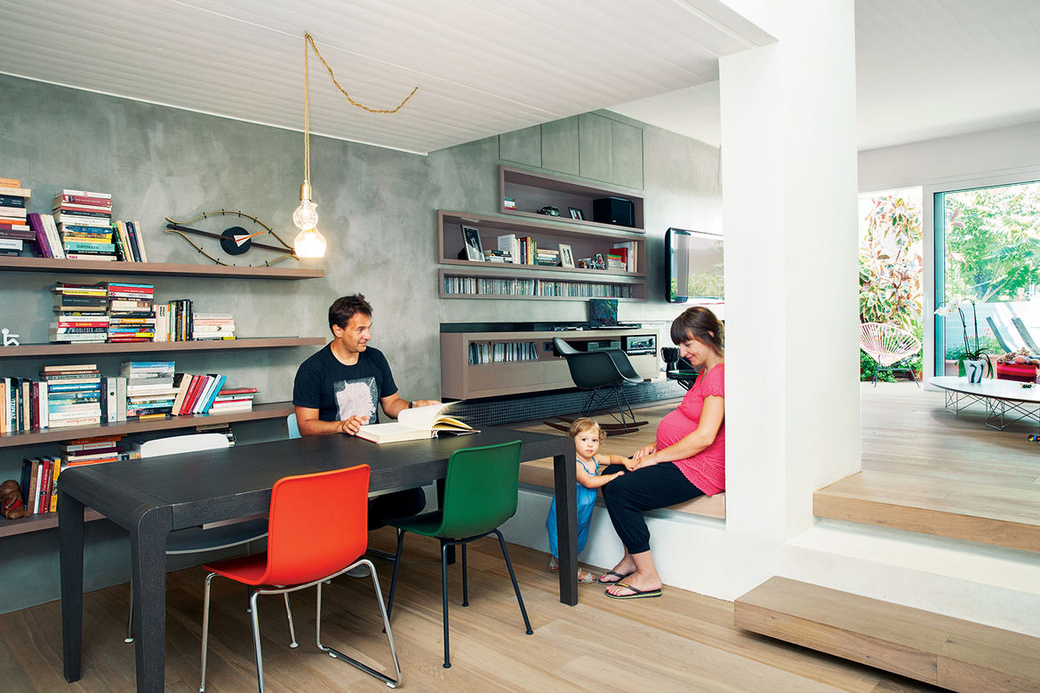 modern lycabettus penthouse apartment dining room with red and green chairs and a hanging pendant light