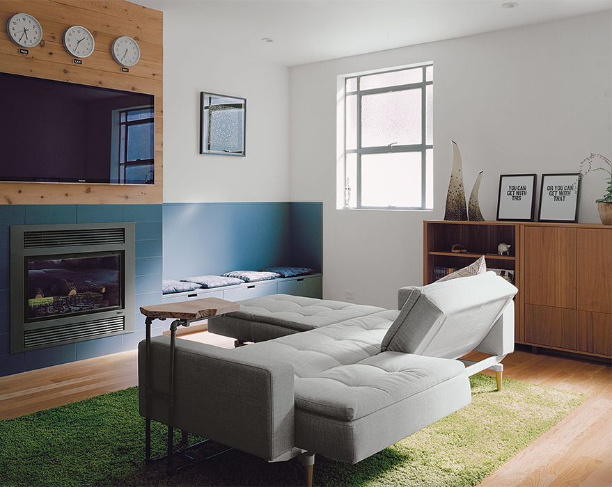 Modern San Francsico renovation with Innovation Living sofa and ottoman, Ikea rug, fireplace and Muji clocks in the living room