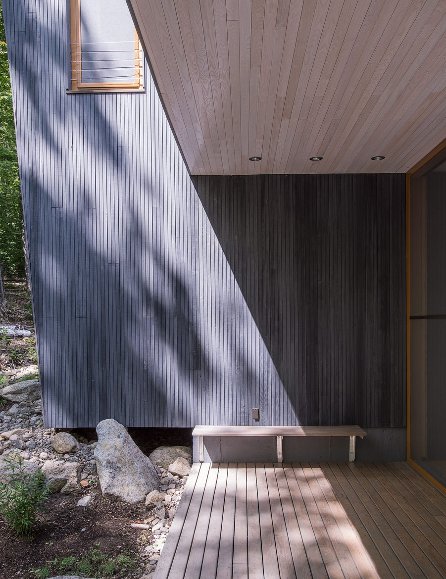 Custom-milled vertical groove tamarack clads the exterior of the upstate New York house