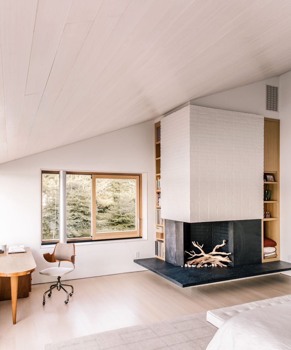 Modern Connecticut summer home renovation with black slate hearth and white masonry by the fireplace in the master bedroom