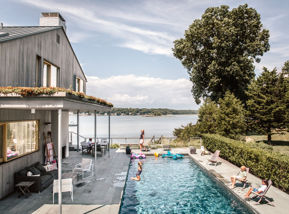 Modern Connecticut summer home renovation with swimming pool, outdoor fireplace, and pie and bluestone deck and pathways