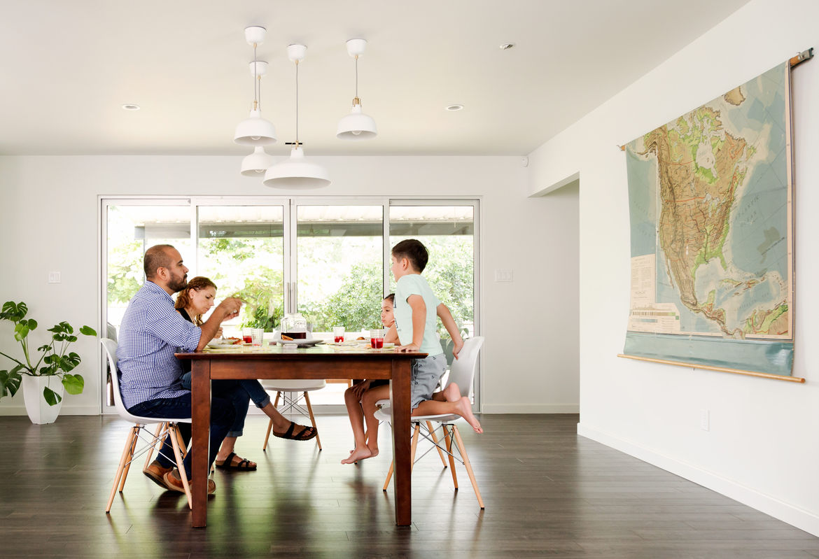 The family relaxes in Eames chairs and enjoys a meal under a collection of pendant lights.