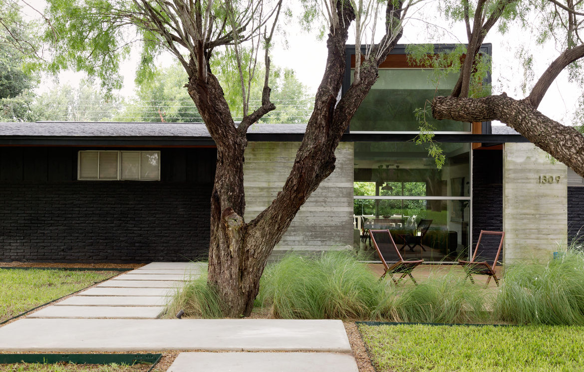 Modern Texas home with concrete beam overhang at entrance.
