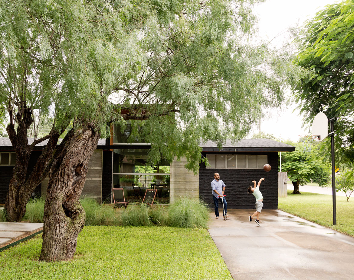 A concrete path wraps around the landscape and leads up to the front door.