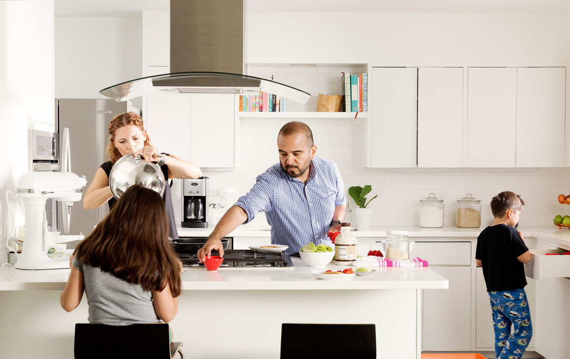 The family gathers around a sleek kitchen with Caesarstone countertops and modern appliances.