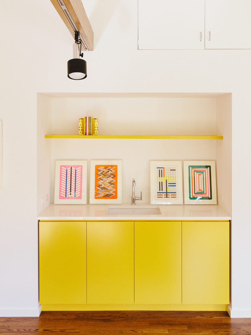 Track lighting puts the spotlight on yellow cabinets and artwork.