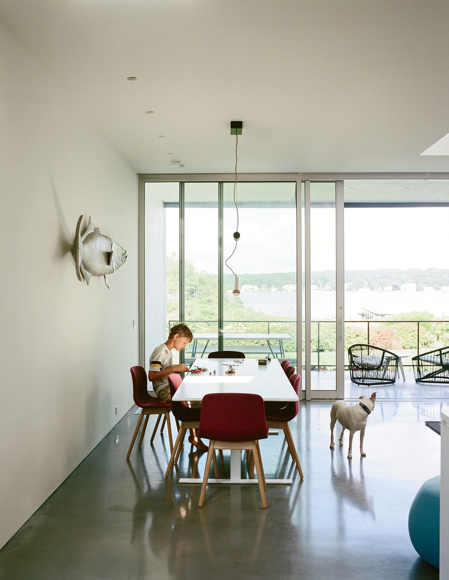 Luxor table by Cappellini, chairs by HAY, and a Counterweight pendant by Fort Standard in dining room of Rhode Island family vacation home by Bernheimer Architecture.
