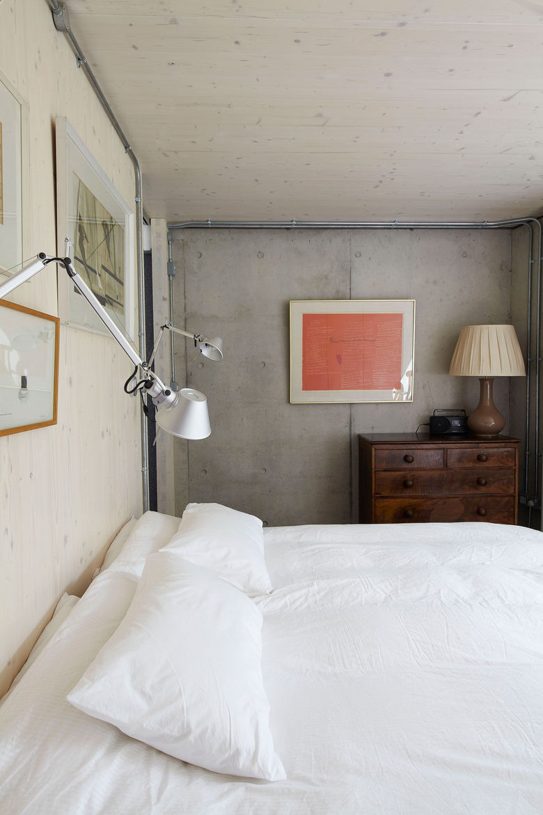 Concrete and timber bedroom with Artemide lights