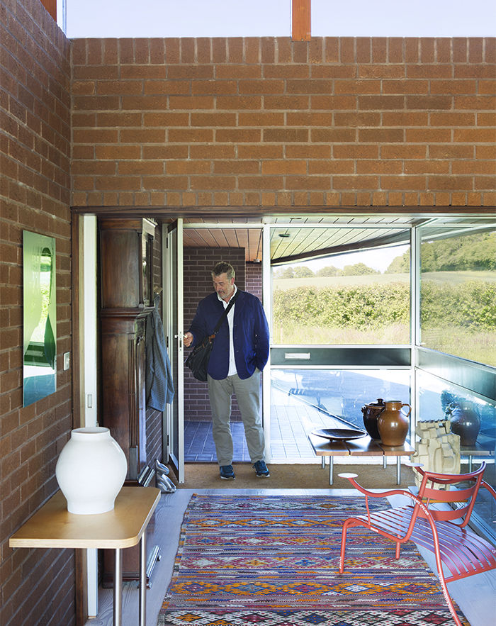 Glass entryway with a Moroccan rug and Jasper Morrison chair