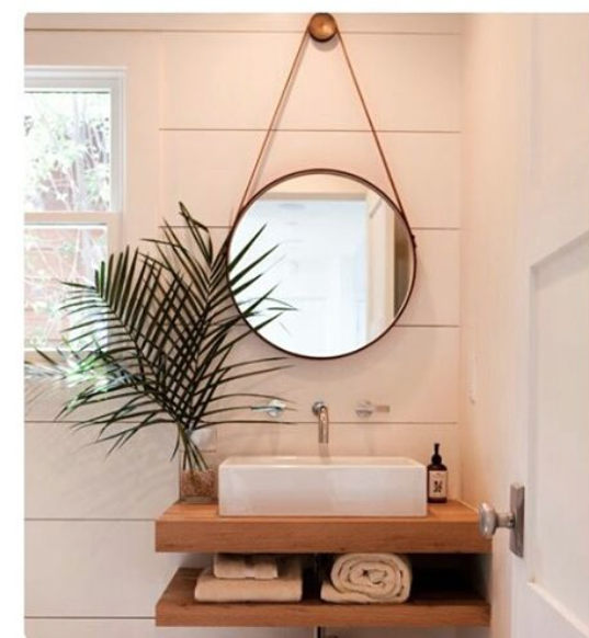 Bathroom with porthole mirror and wood vanity