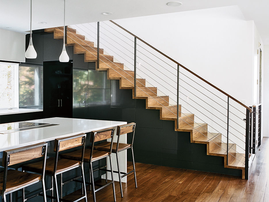 Modern home in North Carolina with rejuvenation pendant lamps, quartz countertops in the kitchen and walnut steps with steel rails