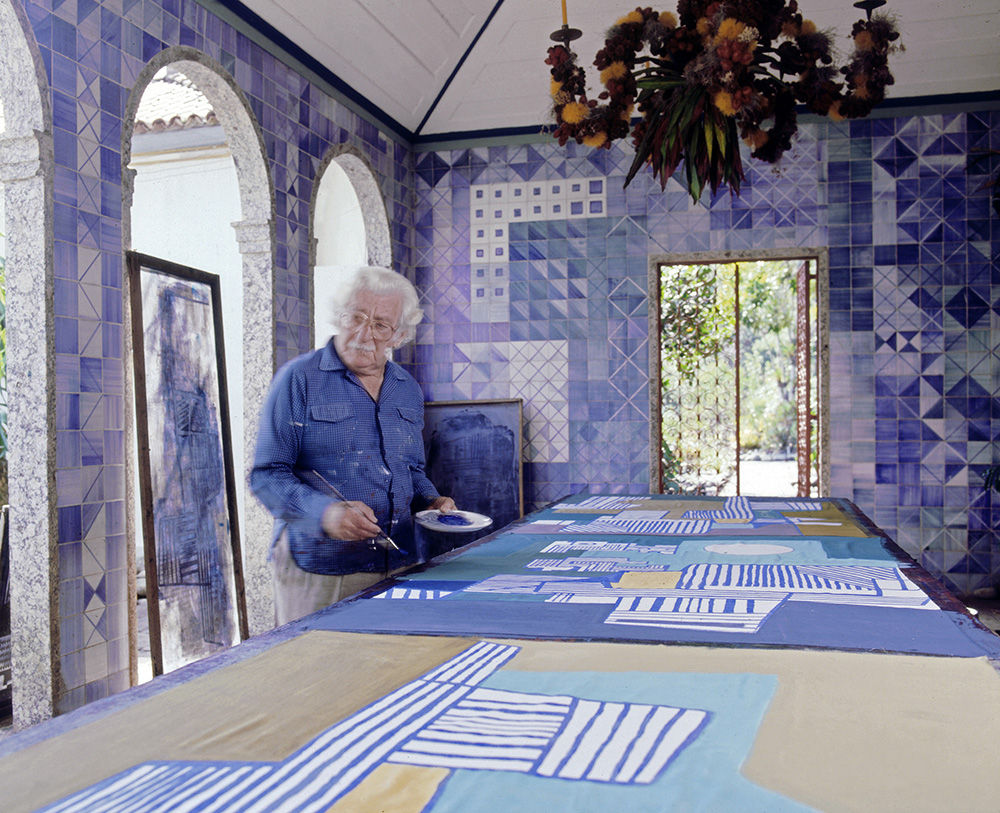 Roberto Burle Marx painting a tablecloth in the loggia of his home, 1980s; the azulejo tile walls and chandelier composed of fruit and flowers on a metal armature are his work.