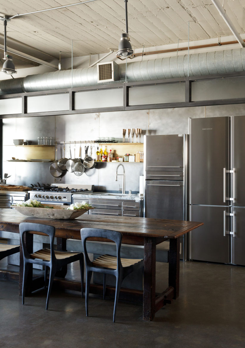 Modern Los Angeles loft kitchen renovation with stainless steel cabinets by Fagor, Henry Hall Designs chairs, CB2 benches and farm table