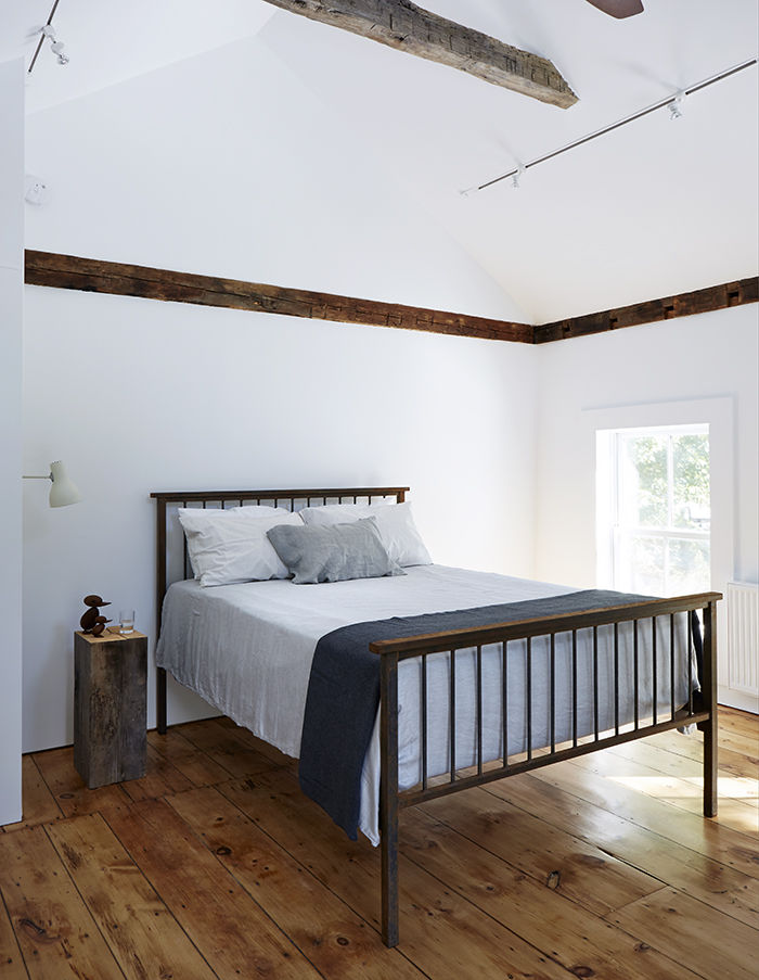 Master bedroom with wood floors and exposed beams in the Twisted Farmhouse