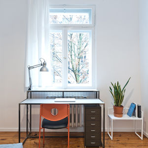 Desk that doubles as radiator cover in small space.